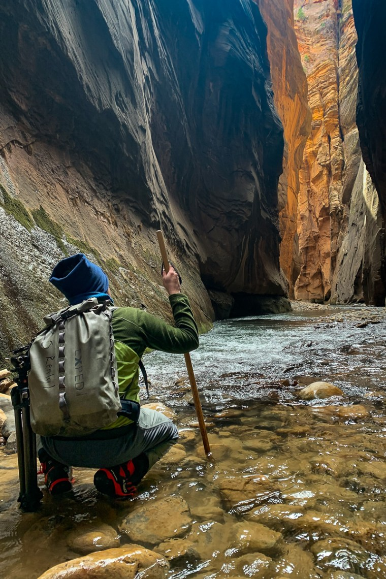 Hiker kneeling in the water of Zion Narrows looking at the orange canyon walls in the distance.