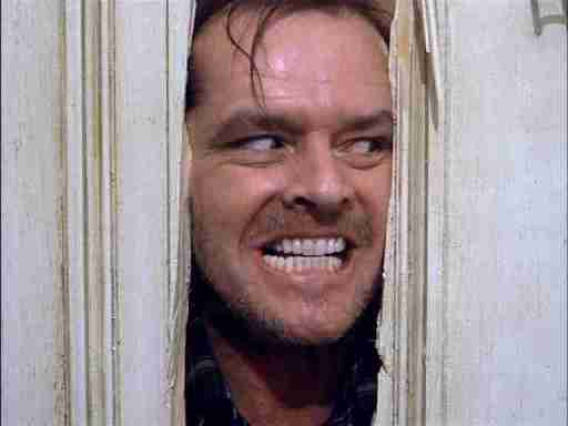 Jack Nicholson looking evil in a doorframe in the movie, The Shining.