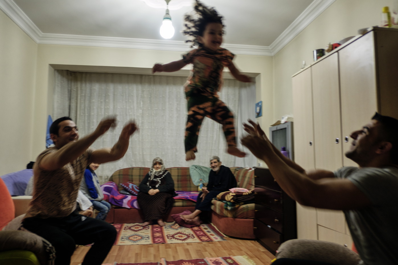31-year-old Mustafa throws his niece to his 39-year-old brother-in-law Ibrahim Shehabi, while their elderly grandparents and other relatives enjoy the scene. Istanbul, Turkey 2016. © Matteo Bastianelli