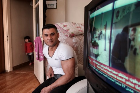39-year-old Ibrahim Shehabi is seen watching bad news regarding his own country on TV, while his niece is seen peeking out from the corridor. Istanbul, Turkey 2016. © Matteo Bastianelli