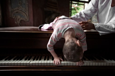 5-year-old Dejan, who was born prematurely with a brain hemorrhage. Dejan, even though he needs to learn how to react to aural stimulus without getting agitated, he adores playing the piano supported by the volunteers. Gornja Bistra, Croatia 2009. © Matteo Bastianelli