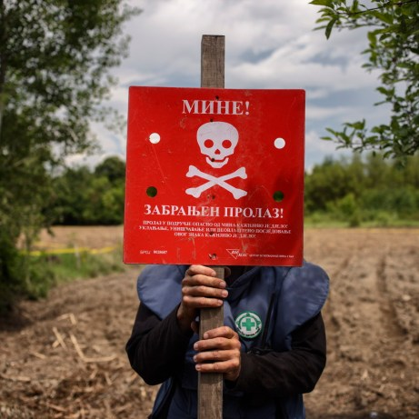 A Norwegian People's Aid deminer is seen planting a warning baninto the ground. Brčko, Brčko District, Bosnia and Herzegovina, 2014.