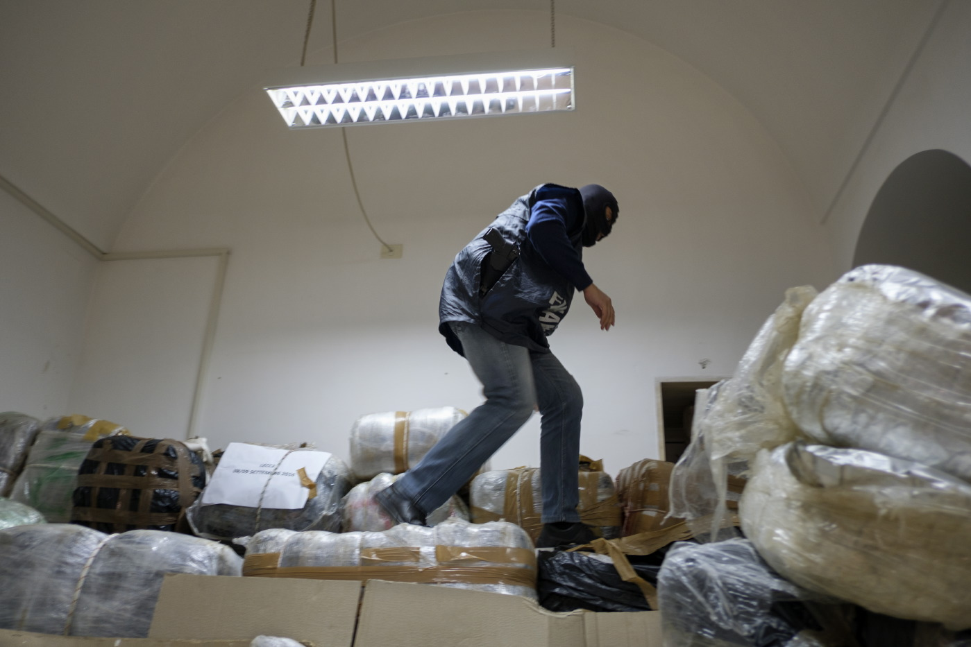 A member of the Counter-narcotics Group (G.O.A.) in the tax unit of the Lecce financial police is seen walking on a pile of bags containing marijuana, to a combined weight of 3 tonnes that were seized in a counter-narcotics operation. Lecce, Italy 2016. © Matteo Bastianelli