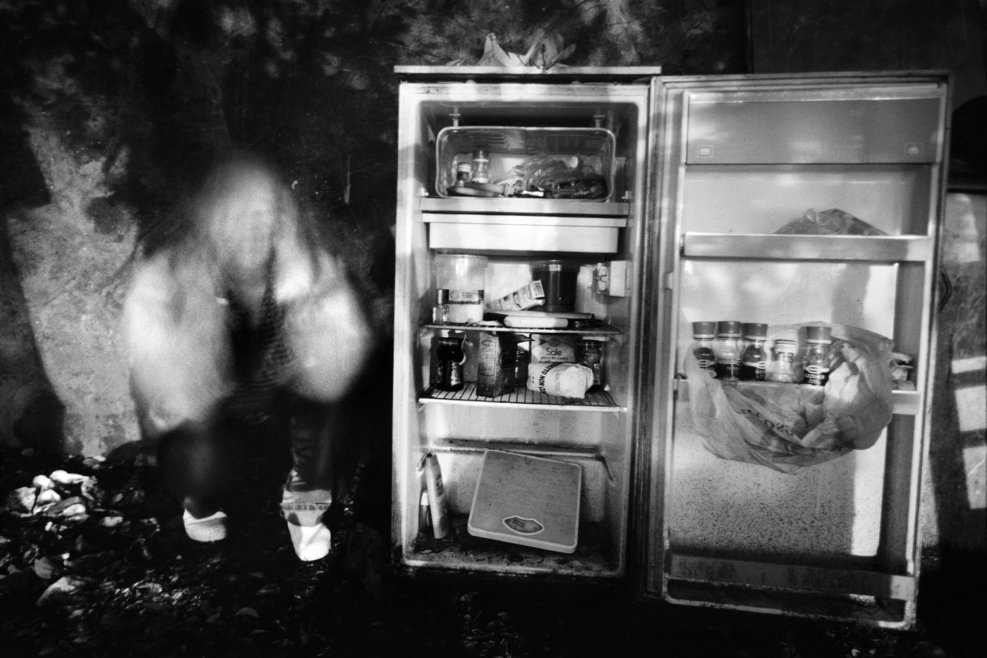 Patrizia, in a moment of discouragement, is seen next to her fridge, in front of the train station. Velletri, Italy 2009. © Matteo Bastianelli