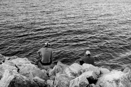 Two asylum seekers are sitting on the beach where they arrived after surviving a perilous sea crossing in a rubber dinghy. Mytilene, Lesbos, Greece 2015. © Matteo Bastianelli