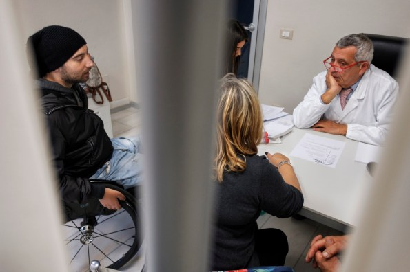 """Doctor Paolo Poli, is seen in his consulting room at the """"Casa di Cura San Rossore"""" facility, along with his assistant Giulia Gianfilippo and his patient Daniele Marioli, accompanied by his parents. Daniele is being treated with medicinal cannabis prescribed by Doctor Poli. Pisa, Italy 2016. © Matteo Bastianelli"""