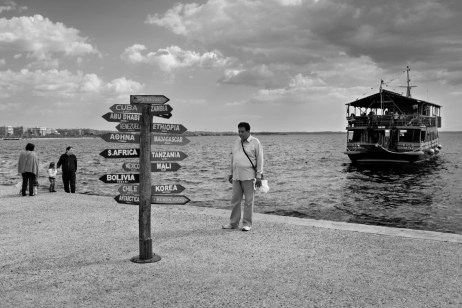 A road sign showing the main tourist destinations in the world, with a boat for holiday-makers in the background. Thessaloniki, Greece 2015. © Matteo Bastianelli