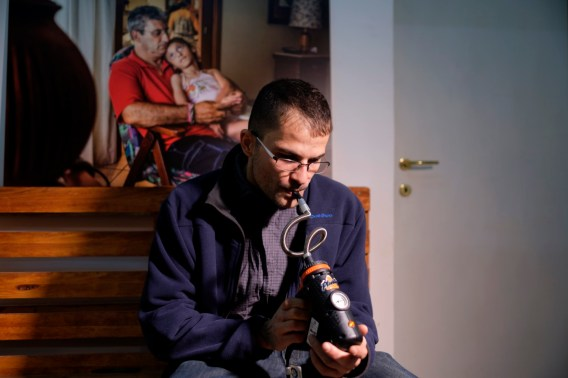 """Carlo Monaco, co-founder of the cultural association """"Canapa caffè"""", is seen using a medical cannabis vaporizer for therapeutic inhalation in the Therapy Room. Rome, Italy 2016. © Matteo Bastianelli"""