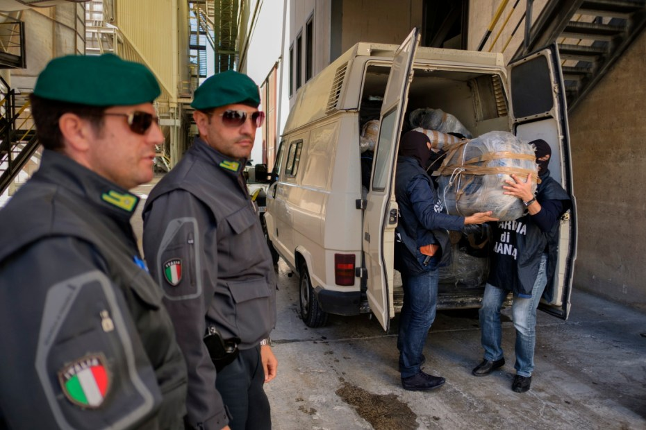Two members of the Counter-narcotics Group (G.O.A.) in the tax unit of the Lecce financial police, start unloading bags of marijuana to be destroyed in an incineration plant. The van contains a load of about a tonne of cannabis coming from Albania and seized in a counter-narcotics operation. Galatina (Lecce), Italy 2016. © Matteo Bastianelli