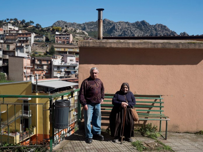 65-year-old barber Roberto Marroni is seen together with 85-year-old woodcutter Gina Cannas. Their village is a world-record holder for male longevity. Villagrande, Italy 2015. © Matteo Bastianelli