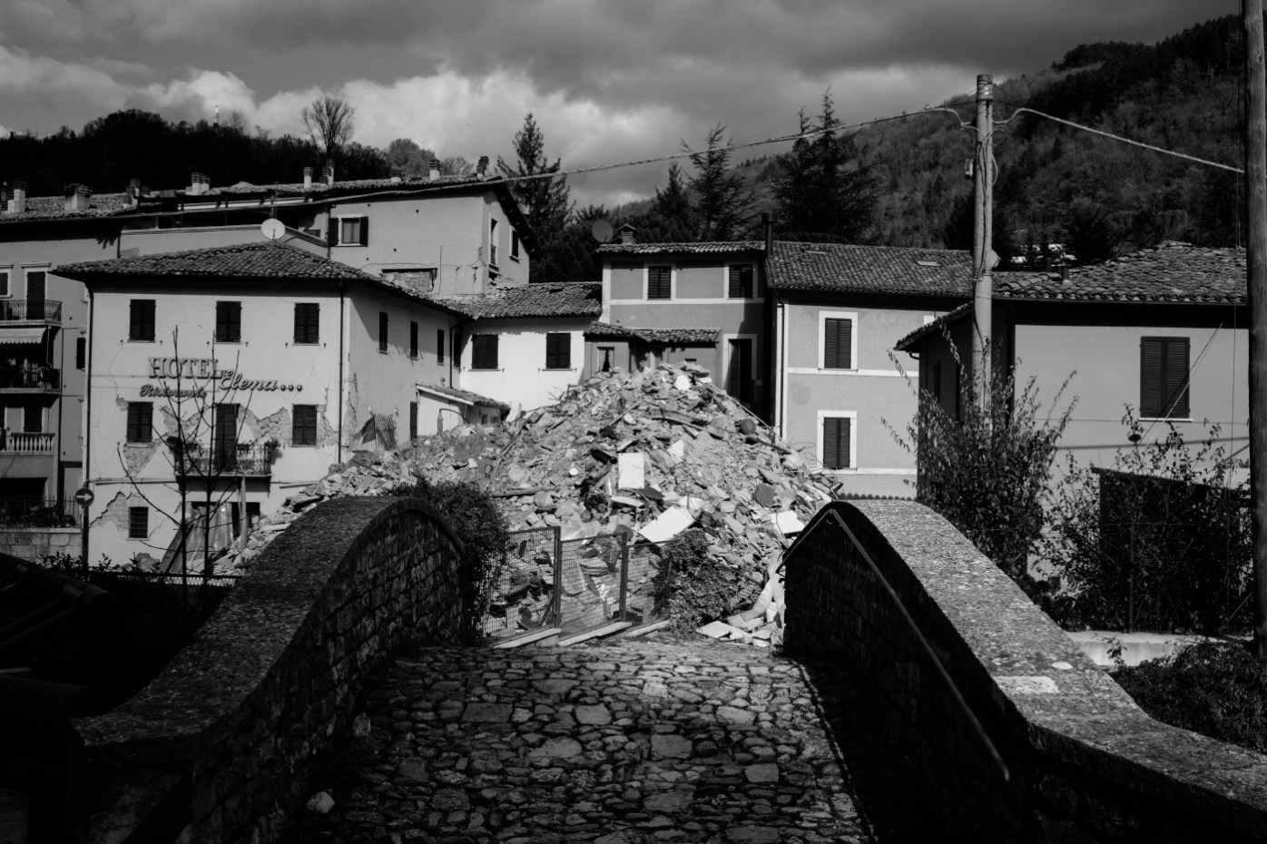 "The ruins of a building in front of others left standing. Visso, Italy 2016. © Matteo Bastianelli for ""La Stampa"""