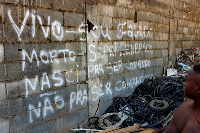 "A guy walks through the favela of Jardim Gramacho, controlled by the Red Command (Comando Vermelho). The writing on the wall says: ""Alive - I'm criticized, dead - I will be remembered, born to be the command, not to be commanded."" Rio de Janeiro, Brazil 2015. © Matteo Bastianelli"