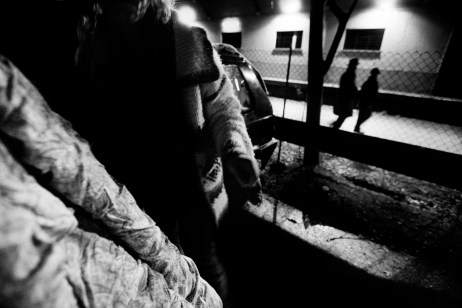 Patrizia puts the duvet in her car while two passers-by are seen in the vicinity of the train station. Velletri, Italia 2009. © Matteo Bastianelli