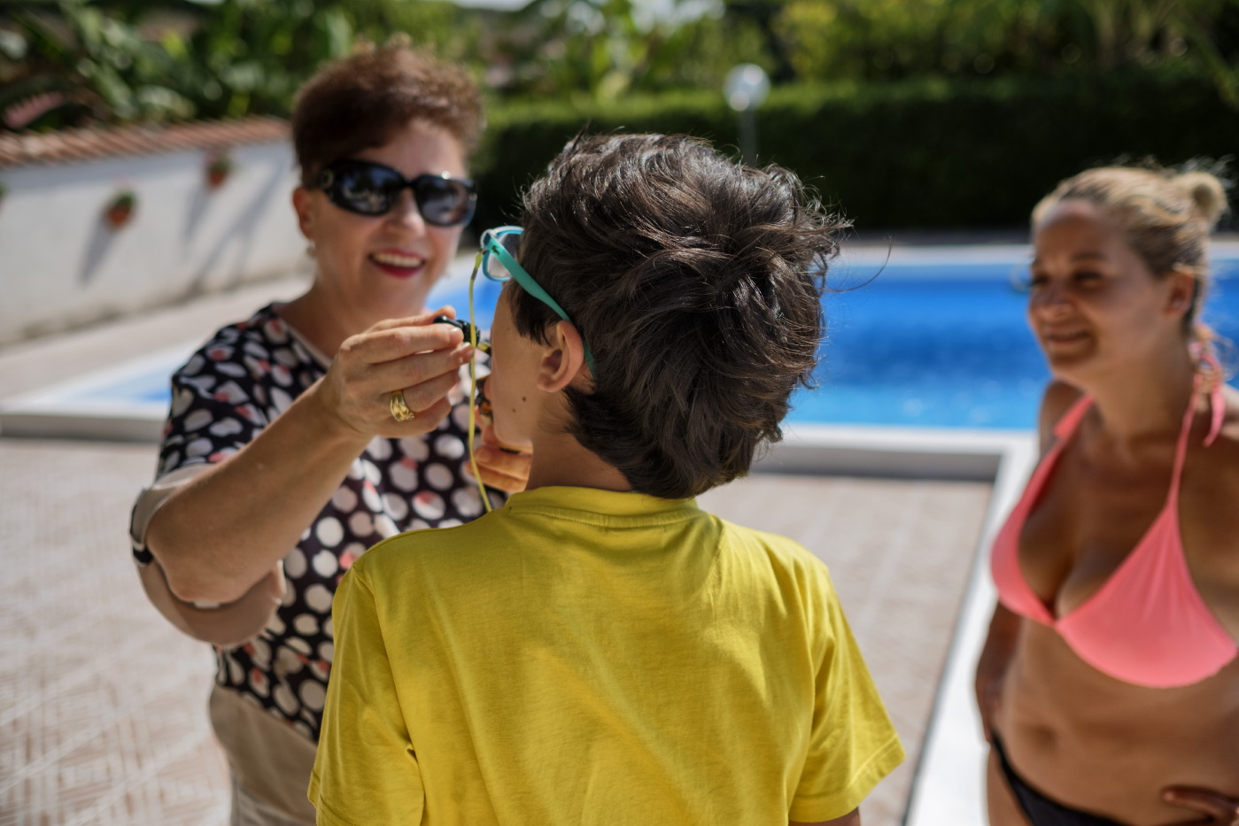 "Clara Gucciullo administers CBD oil extract (cannabidiol) for therapeutic purposes to his 12-year-old foster child Francesco, who suffers from autism, while the co-founder of the ""Cannabis Cura Sicilia"" association, Florinda Vitale, watches them. Lentini (Siracusa), Italy 2016. © Matteo Bastianelli"