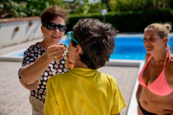 """Clara Gucciullo administers CBD oil extract (cannabidiol) for therapeutic purposes to his 12-year-old foster child Francesco, who suffers from autism, while the co-founder of the """"Cannabis Cura Sicilia"""" association, Florinda Vitale, watches them. Lentini (Siracusa), Italy 2016. © Matteo Bastianelli"""