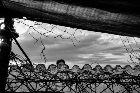 A woman is seen in the vicinity of a fence. L'Aquila, Italy 2009. © Matteo Bastianelli