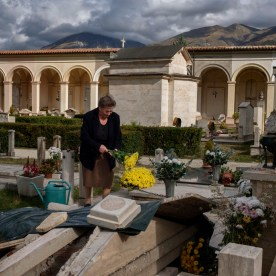 A woman brings flowers to her parents' grave, badly damaged by the earthquake. Norcia, Italy 2016. © Matteo Bastianelli