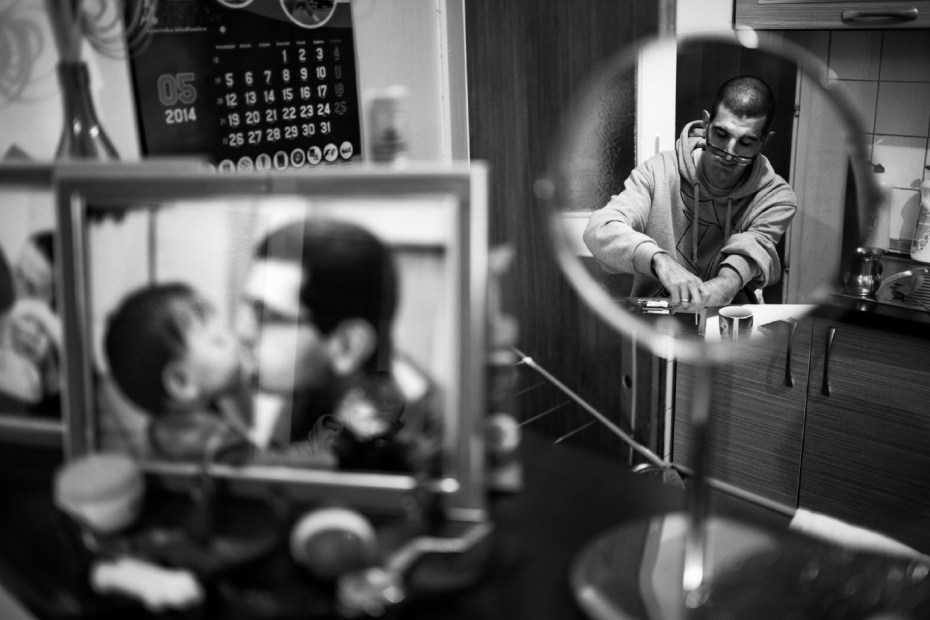 Adis Smajić, 32-year-old, is seen working on a laptop in his house. He is unemployed like 40% of the population and lives with a disability pension, but he tries also to gain some money doing small jobs on electronic devices. Sarajevo, Bosnia and Herzegovina 2014. © Matteo Bastianelli