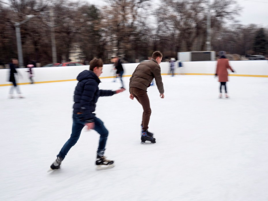 Children and families ice-skating on an outdoor rink in the city-center. Chisinau, Moldova 2014. © Matteo Bastianelli