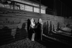Two women in a stadium used to store the coffins for a collective funeral of the 284 victims of Bosnian Serbs ethnic cleansing in Prijedor. The bodies were exhumed from a huge mass grave discovered in Tomasica 22 years after 435 human beings were killed and hidden on that site. Kozarac, Bosnia and Herzegovina, 2014. © Matteo Bastianelli