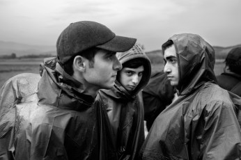 Three Syrian youths taking a break on their way to the border between Greece and the Republic of North Macedonia. Evzoni, Greece 2015. © Matteo Bastianelli