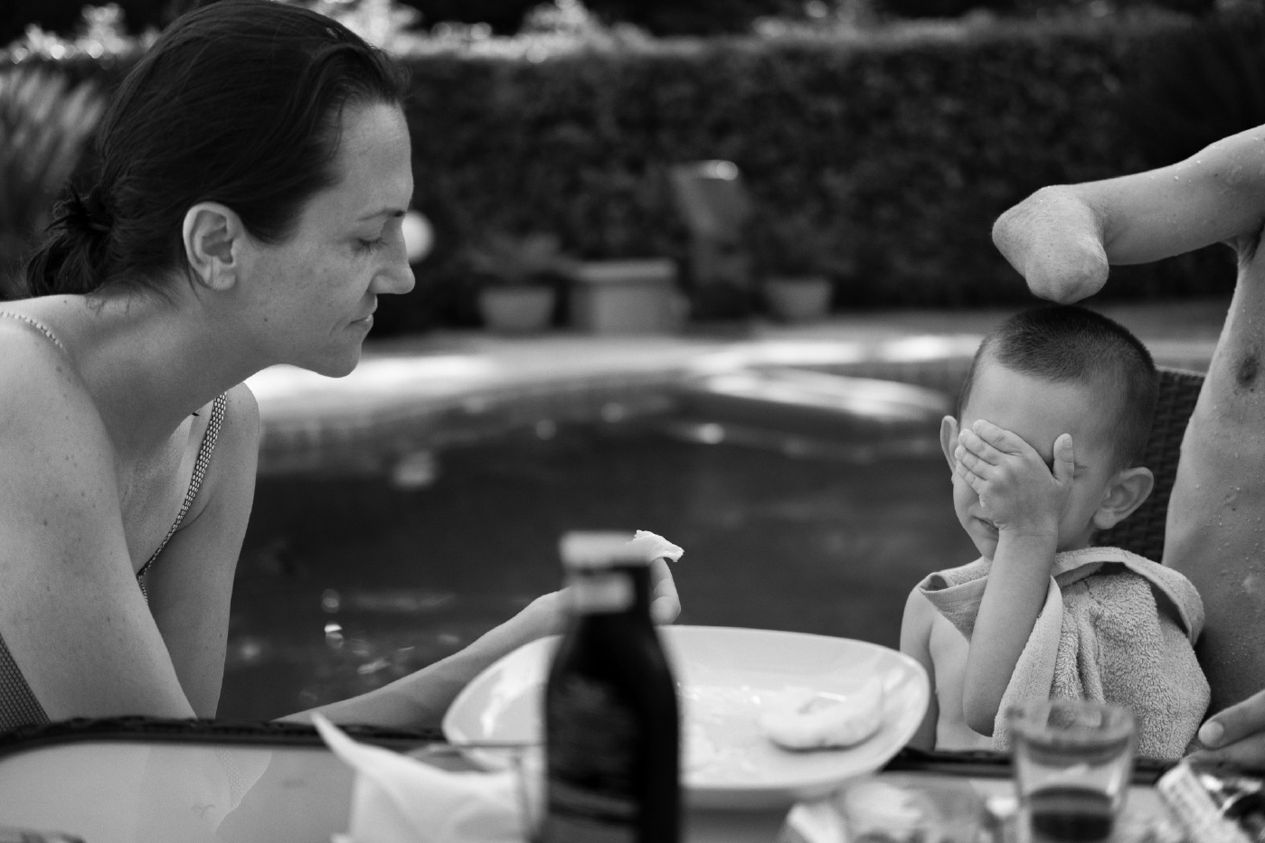 Naida feeds her 3-year-old son Alen who sits by the pool with his father Adis. The Smajic family travelled to Rome for the replacement of Adis' old prosthetic eye. Velletri, Italy 2016. © Matteo Bastianelli