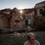 70-year-old Maria Pia Cortelli in the courtyard of her house. On the background, her neighbor's house destroyed by the earthquake. Norcia, Italy 2016. © Matteo Bastianelli
