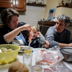 Adele Pontani sitting at the table with her husband Fabio Allegrini and their nephew. Norcia, Italy 2016. © Matteo Bastianelli