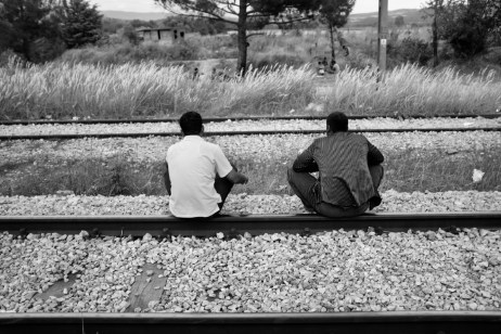 Two asylum seekers take a rest on the railway tracks in the buffer zone between Greece and the Republic of North Macedonia. Idomeni, Greece 2015. © Matteo Bastianelli