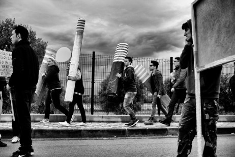 Some young men are seen carrying reproductions of ILVA chimneys during a protest march. Statte (Taranto), Italy 2014. © Matteo Bastianelli