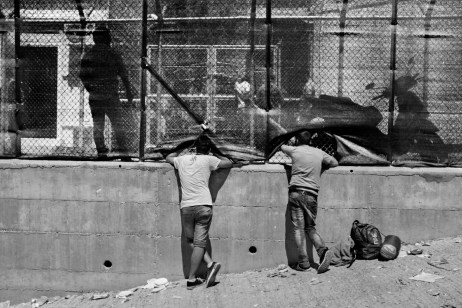 Two asylum seekers look through a shade cloth at the former military base of Moria, turned into a makeshift refugee camp where hundreds of asylum seekers are hosted without access to the basic needs of life, including food, drinking water, bathroom or shelter. Moria, Lesbos, Greece 2015. © Matteo Bastianelli