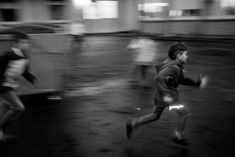 A Serbian asylum seeker runs away while playing with other friends inside a refugee camp. Warstein, Germany 2015. © Matteo Bastianelli