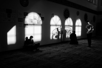 "24-year-old Syrian refugee Hani Al Masalmeh reads the Koran in the ""Fatih Camii"" mosque, while waiting for his 23-year-old cousin Mohamad to join him, as a man is praying in the middle of the room. Meschede, Germany 2016. © Matteo Bastianelli"