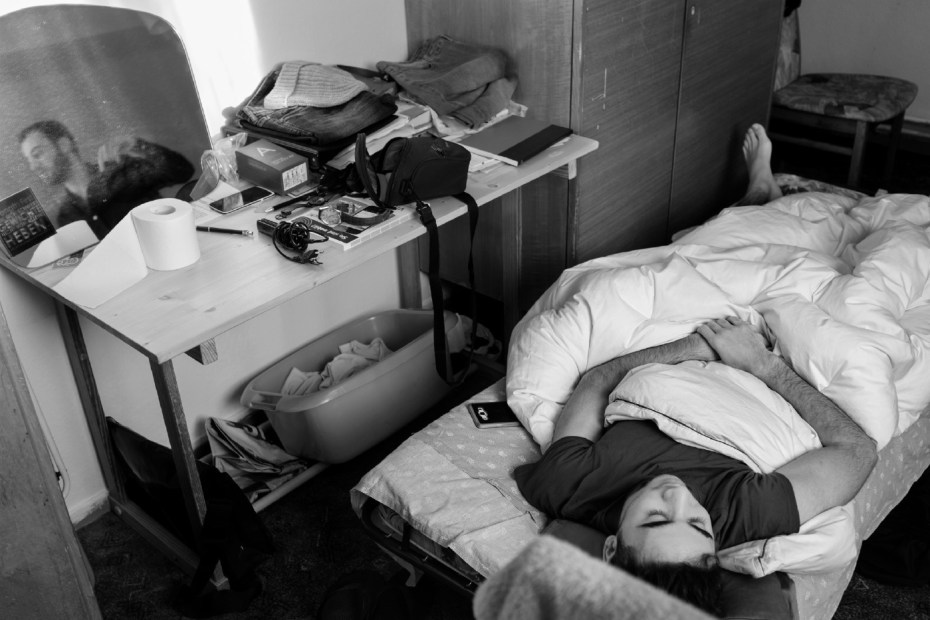 23-year-old Syrian refugee Mohamad Al Masalmeh asleep with his phone next to him while his cousin is getting ready to go out. They have been living together in a flat paid for by the German welfare state for over a year. Their families are still trapped in Syria. Belecke (Warstein), Germany 2016. © Matteo Bastianelli