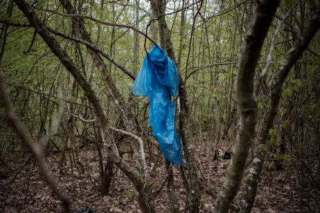 "A raincoat hanging from a tree branch. In the forests between Bulgaria and Turkey, there are a large number of personal belongings and clothes left behind by border crossers. Volunteers from the ""Vasil Levski"" Bulgarian Military Veterans Union believe illegal crossings are the work of soldiers and terrorists, not of migrants. Yasna Polyana, Bulgaria 2017. © Matteo Bastianelli"
