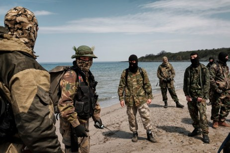 "Some volunteers from the ""Vasil Levski"" Bulgarian Military Veterans Union are seen on a beach in the vicinity of the Nestinarka camp-site on the Black Sea coast. Their movement has more than 800 members divided in groups of 30-40 people who take turns patrolling the Bulgarian-Turkish border to prevent illegal crossings through the forest. They wear ski masks to protect their identity; ISIS has put out a reward for some of them. Tsarevo, Bulgaria 2017. © Matteo Bastianelli"