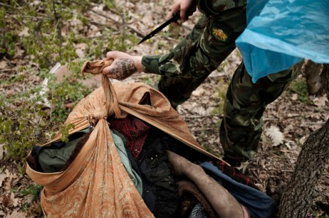 "A volunteer from the ""Vasil Levski"" Bulgarian Military Veterans Union opens a bundle of clothing with a knife, after finding it on the side of a road, in the vicinity of a forest. Yasna Polyana, Bulgaria 2017. © Matteo Bastianelli"