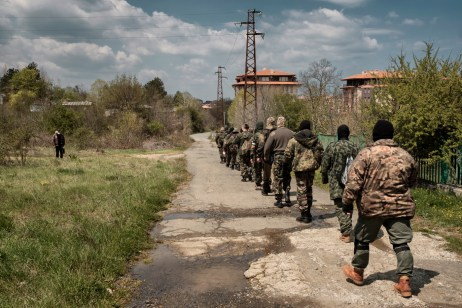 "Volunteers from the ""Vasil Levski"" Bulgarian Military Veterans Union and from the ""BNO Shipka"" are seen marching on their way back from the forest where they have been training, while a local resident observes them. Tsarevo, Bulgaria 2017. © Matteo Bastianelli"