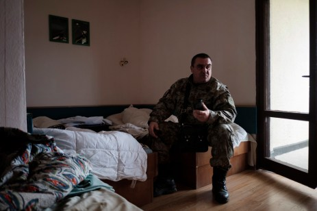 "A commander of the ""Vasil Levski"" Bulgarian Military Veterans Union is seen in a room at a former fitness center turned into a base for volunteers, in the vicinity of the Nestinarka camp-site. Tsarevo, Bulgaria 2017. © Matteo Bastianelli"
