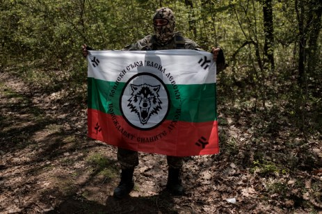 "A volunteer from the ""Vasil Levski"" Bulgarian Military Veterans Union shows the banner of his movement, before climbing the Strandja Mountain, near the border with Turkey. Yasna Polyana, Bulgaria 2017. © Matteo Bastianelli"