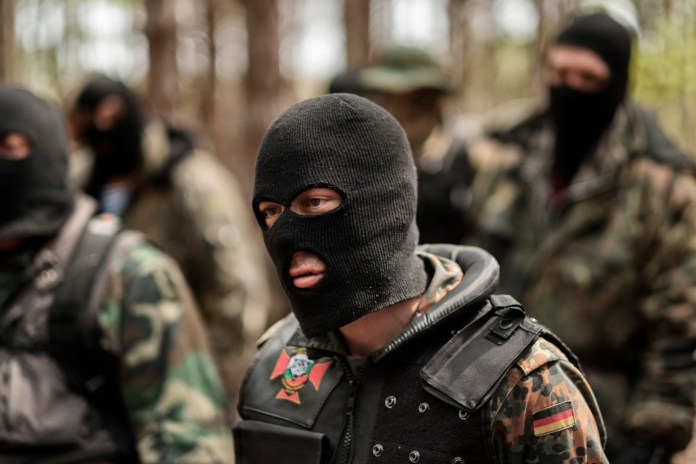 "A volunteer from the ""Vasil Levski"" Bulgarian Military Veterans Union is seen assembling with other members during a drill in the forest near Nestinarka camp-site. Four to five times a month, they train like an army to face what they consider an invasion to ""Islamize"" Europe. Tsarevo, Bulgaria 2017. © Matteo Bastianelli"