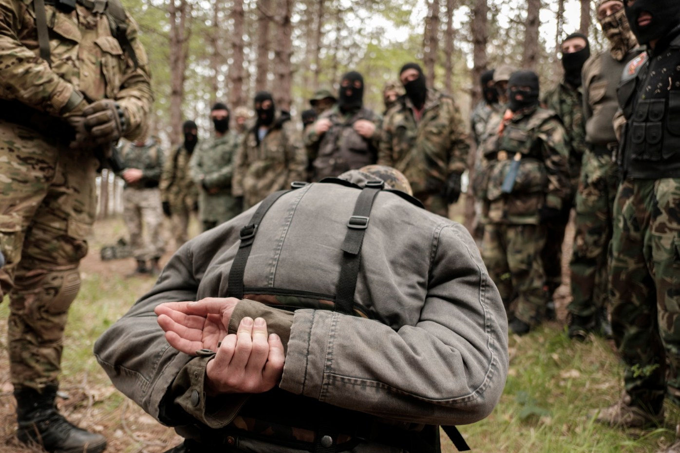 "A volunteer from the ""Vasil Levski"" Bulgarian Military Veterans Union is seen kneeling during a drill in which the simulation of the capture of a man was carried out in the forest near Nestinarka camp-site. Tsarevo, Bulgaria 2017. © Matteo Bastianelli"