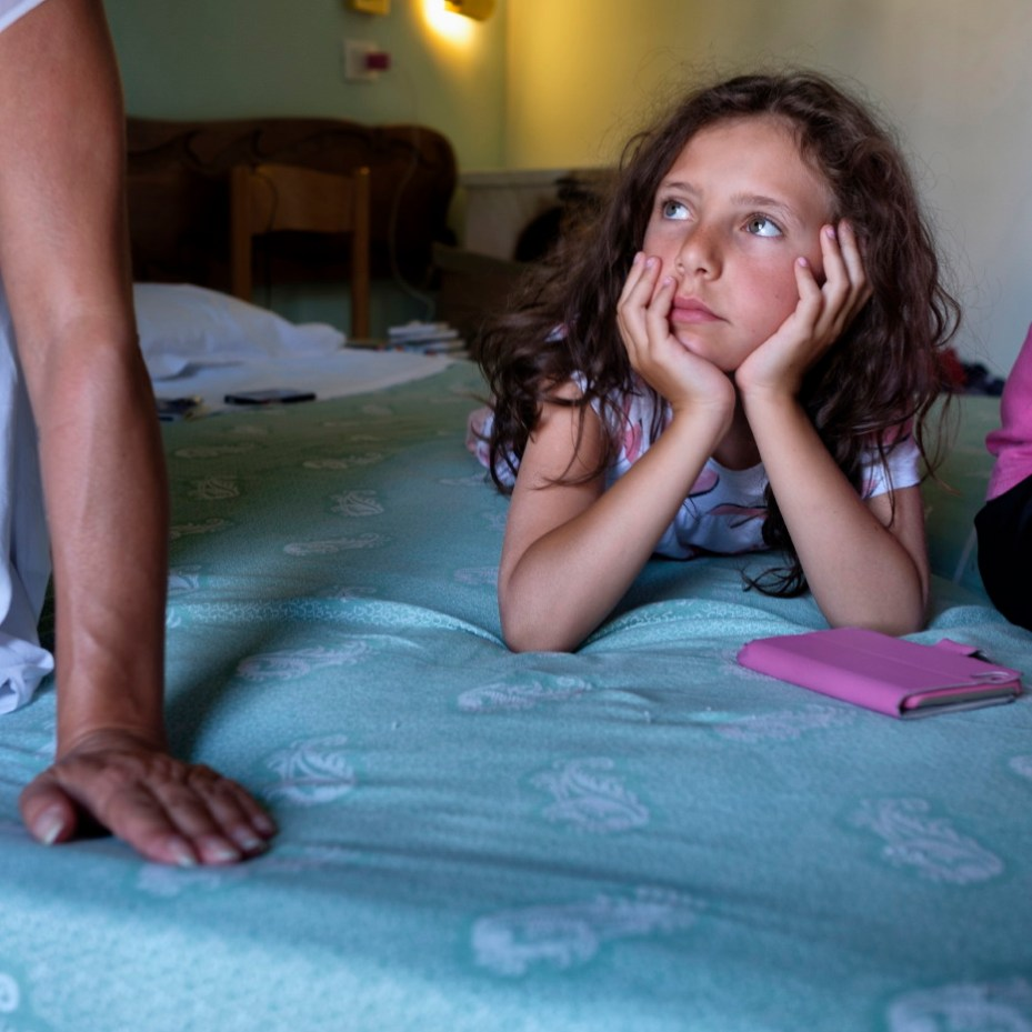 9-year-old Anastasia Paganelli, is seen lying on the bed with her parents in the hotel room where they are temporarily staying. Grottammare, Italy 2017. © Matteo Bastianelli