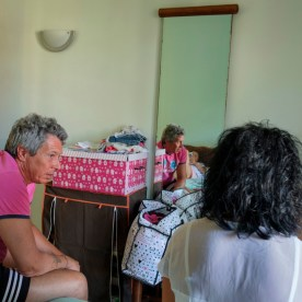 Giambattista and Annunziatina are seen with their daughter Anastasia on the bed of the hotel room where they are temporarily staying. Following the earthquake of 24 August 2016, thousands of evacuees have been moved to the Adriatic coast awaiting the earthquake-proof wooden houses. Grottammare, Italy 2017. © Matteo Bastianelli