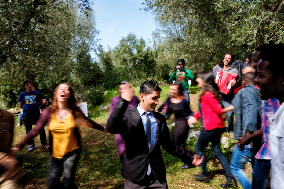 Some young men, housed in the SPRAR centre (System of Protection for Asylum Seekers and Refugees) in the Salento area, are seen dancing and singing with a band during the hemp seed planting party. Castiglione d'Otranto, Italy 2016. © Matteo Bastianelli