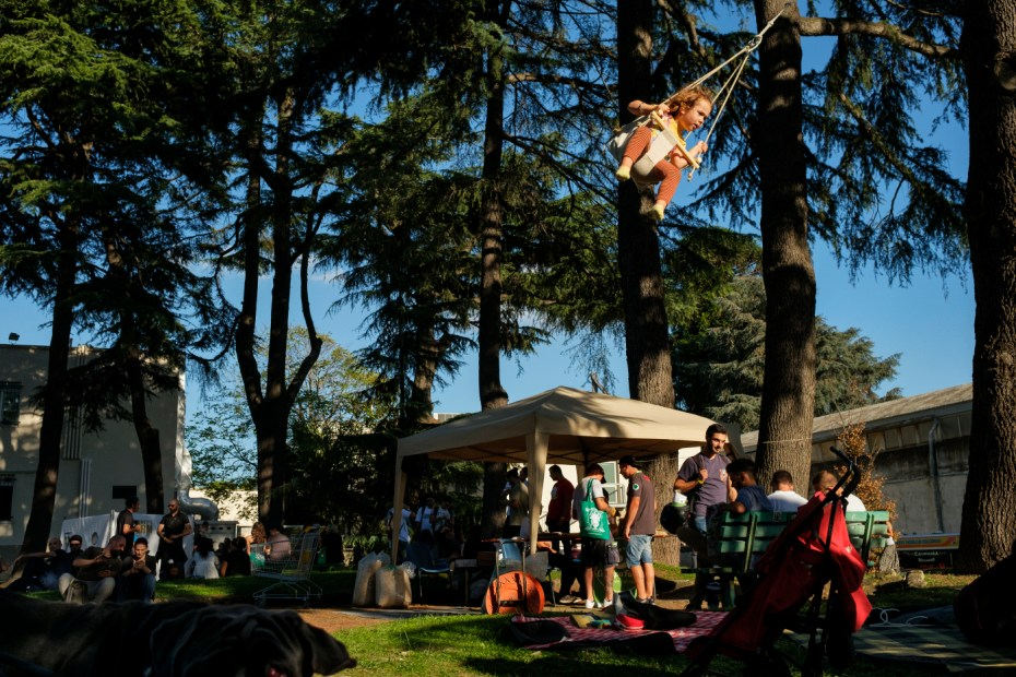 "Some visitors at the industrial hemp and medical cannabis fair ""Canapa in Mostra"", are seen relaxing in the garden at the complex while a child plays on a swing hanging from a tree branch. Naples, Italy 2016. © Matteo Bastianelli"