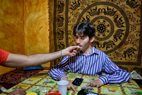36-year-old Alberico Nobile, who was left quadriplegic after a car accident, is seen smoking cannabis in his house with the help of his friend Vincenzo. Due to his disease, Alberico's parents and friends roll cannabis cigarettes every hour to give him his therapy. Talsano (Taranto), Italy 2016. © Matteo Bastianelli