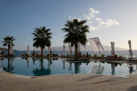 """Some people are seen resting around the outdoor pool of the """"Santa Quaranta"""" five-star hotel owned by fugitive criminal Klement Balili. Many tourists who are staying there don't know that its owner is wanted by the DEA, a United States federal law enforcement agency, and by the Greek police. Sarandë, Albania 2017. © Matteo Bastianelli"""