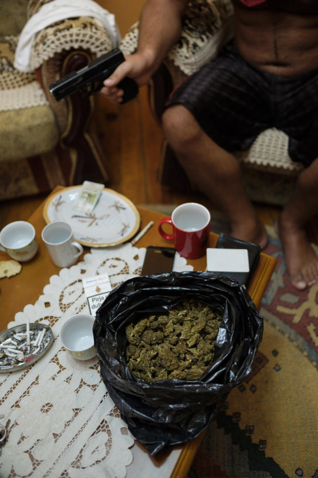 A drug trafficker is seen holding the gun that he always carries with him, while seated around a table with marijuana and cocaine on it, drugs that he illegally holds in a house in Albania 2017. © Matteo Bastianelli