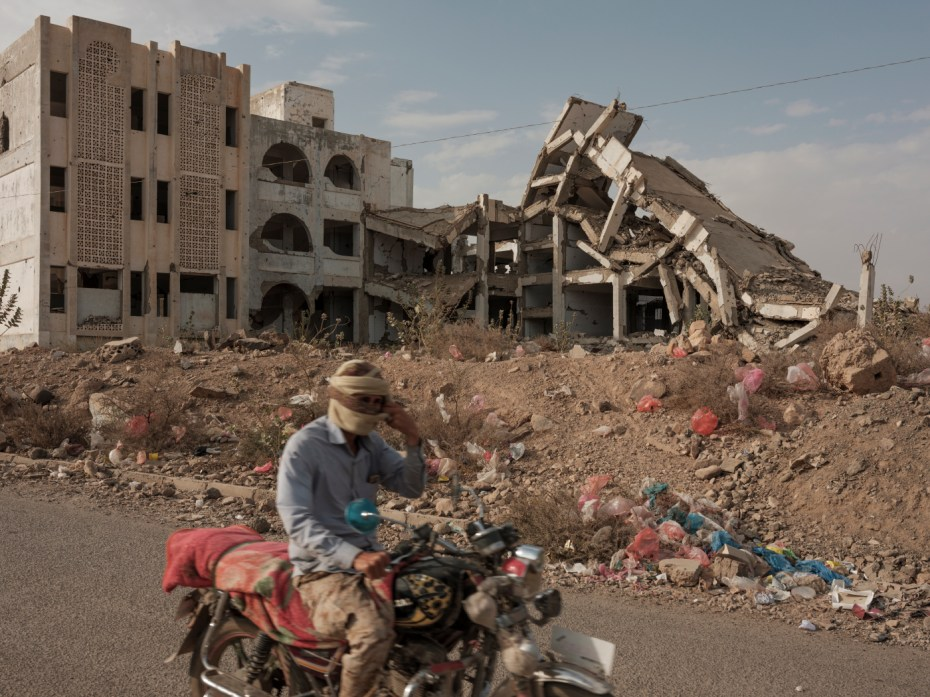 A motorcyclist rides past an area strewn with garbage next to a school, destroyed by a Saudi-led coalition air-strike. Ad Dhale, Yemen 2018. © Matteo Bastianelli